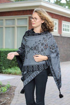 Grijze omslagdoek met zwart en bloemen gebreid van alpaca wol in peru, sociaal verantwoord gemaakt.